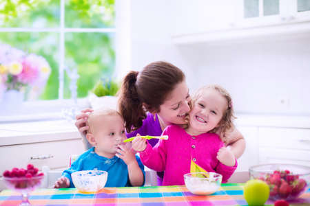 sister: Family having breakfast in a white sunny kitchen. Young mother feeding two kids, eating fruit and dairy. Healthy nutrition for children - yogurt, strawberry and apple. Parent with toddler kid and baby cooking morning meal. Stock Photo