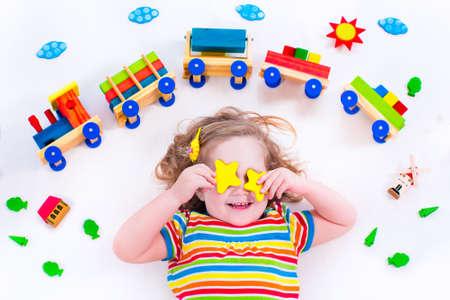 Niño que juega con el tren de madera. Ferrocarril de juguete para los niños. Niño del niño en la guardería. Juguetes educativos para preescolar y jardín de infantes niño. La niña en la guardería.