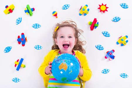 preescolar: Ni�o jugando con aviones de madera. Preescolar chico volando alrededor del mundo. Ni�os viajando y jugando. Los ni�os en la guarder�a o jard�n de infantes. Ver desde arriba. Foto de archivo