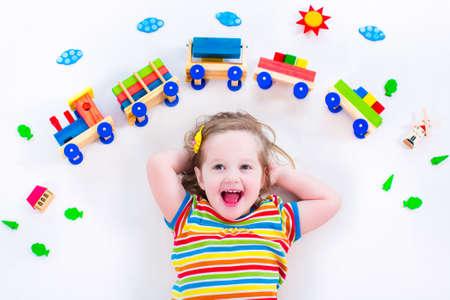 Kinderen spelen met houten trein. Speelgoed spoorlijn voor kinderen. Peuter jongen op dag zorg. Educatief speelgoed voor voorschoolse en kleuterschool kind. Meisje bij de kinderopvang. Stockfoto