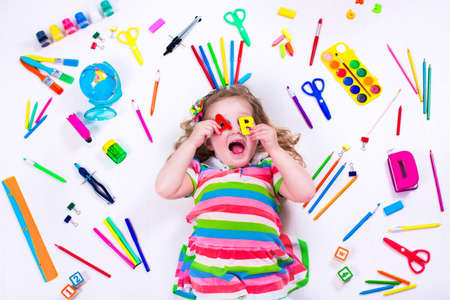 Child with draw and paint supplies. Kids happy to go back to school. Preschool kid learning and studying. Creative children at kindergarten. Office supply objects collection. Banco de Imagens