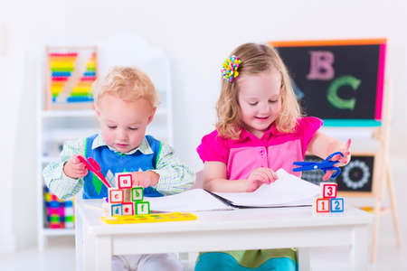 learning: Kids at preschool. Two children drawing and painting at kindergarten. Boy and girl happy to go back to school. Toddler kid and baby learn letters at child care. Class room with chalkboard and abacus