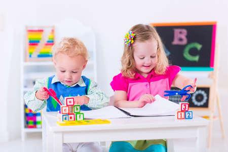Kinderen op de kleuterschool. Twee kinderen tekenen en schilderen op de kleuterschool. Jongen en meisje blij om terug naar school te gaan. Peuter jongen en baby leren brieven bij de kinderopvang. Klaslokaal met bord en telraam