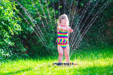 family gardening: Child playing with garden sprinkler. Kid in bathing suit running and jumping. Kids gardening. Summer outdoor water fun. Children play with gardening hose watering flowers. Stock Photo