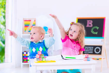 class room: Kids at preschool. Two children drawing and painting at kindergarten. Boy and girl happy to go back to school. Toddler kid and baby learn letters at child care. Class room with chalkboard and abacus