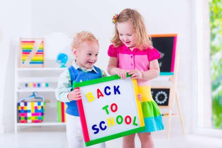 kinder: Los niños en edad preescolar. Dos niños de dibujo y pintura en el jardín de infantes. Niño y niña feliz de volver a la escuela. Niño niño y el bebé aprenden letras en el cuidado de niños. Sala de clase con la pizarra y el ábaco Foto de archivo