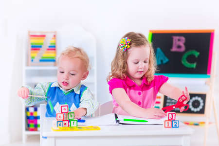 drawing room: Kids at preschool. Two children drawing and painting at kindergarten. Boy and girl happy to go back to school. Toddler kid and baby learn letters at child care. Class room with chalkboard and abacus