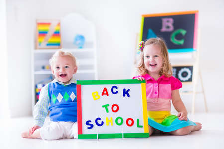 baby room: Kids at preschool. Two children drawing and painting at kindergarten. Boy and girl happy to go back to school. Toddler kid and baby learn letters at child care. Class room with chalkboard and abacus