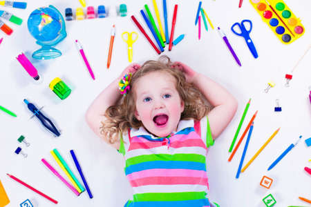 nursery school: Child with draw and paint supplies. Kids happy to go back to school. Preschool kid learning and studying. Creative children at kindergarten. Office supply objects collection. Stock Photo