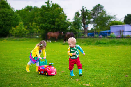 Family on a horse farm in summer. Brother and sister riding a toy car. Outdoor fun for children. Kids playing with pets. Child feeding an animal. Girl and little boy play together in the garden.
