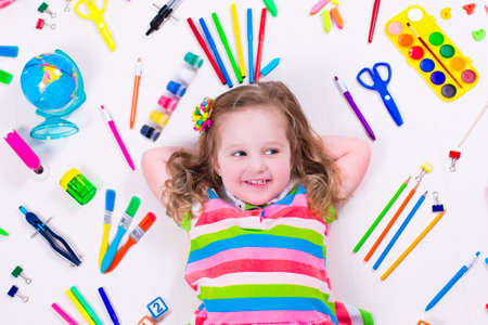 school book: Child with draw and paint supplies. Kids happy to go back to school. Preschool kid learning and studying. Creative children at kindergarten. Office supply objects collection. Stock Photo