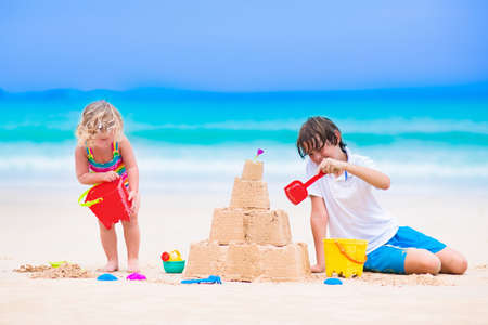 kids playing: Kids playing on a beach. Two children build a sand castle at the sea shore. Family vacation on a tropical island. Boy and girl digging with toy spade and kid spade. Traveling with young child.