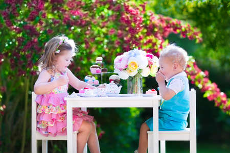 Tea garden party for kids. Child birthday celebration. Little boy and girl play outdoor drinking hot chocolate and eating cake. Children eat sweets. Kid event with toy dish and flower decoration. photo