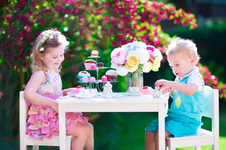 eating in the garden: Tea garden party for kids. Child birthday celebration. Little boy and girl play outdoor drinking hot chocolate and eating cake. Children eat sweets. Kid event with toy dish and flower decoration. Stock Photo