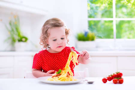 hungry children: Kids eat pasta. Healthy lunch for children. Toddler kid eating spaghetti Bolognese in a white kitchen at home. Preschooler child cooking noodles with tomato and pepper for dinner. Food for family.