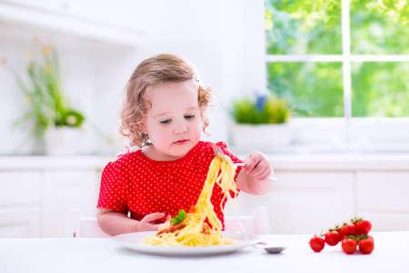 pastas: Los niños comen pasta. Almuerzo saludable para los niños. Chico Niño que come espaguetis a la boloñesa en una cocina blanca en casa. Preescolar niño cocinar fideos con tomate y pimiento para la cena. Alimentos para la familia. Foto de archivo