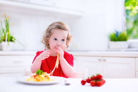 a little dinner: Kids eat pasta. Healthy lunch for children. Toddler kid eating spaghetti Bolognese in a white kitchen at home. Preschooler child cooking noodles with tomato and pepper for dinner. Food for family.
