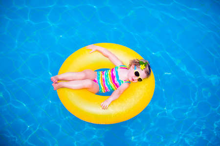 blue eyes girl: Child in swimming pool. Little girl playing in water. Vacation and traveling with kids. Children play outdoors in summer. Kid with inflatable ring toy. Swim wear and sun glasses for UV protection. Stock Photo
