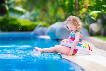Kids in swimming pool. Children swim outdoors. Toddler child during vacation in a tropical resort with palm trees. Little girl playing on a beach. Active kid in summer with colorful toy floating ring. Banque d'images