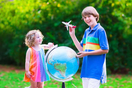 Two happy children, cute curly toddler girl and a smiling school age boy play with toy airplanes flying over the globe dreaming of traveling around the world. Kids fly and travel with airplane. photo