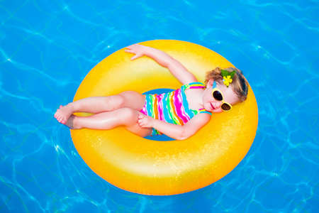 Child in swimming pool. Little girl playing in water. Vacation and traveling with kids. Children play outdoors in summer. Kid with inflatable ring toy. Swim wear and sun glasses for UV protection. Banco de Imagens