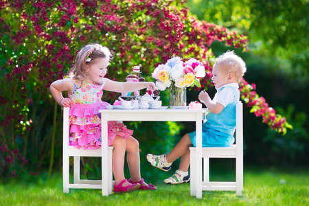 kids birthday party: Tea garden party for kids. Child birthday celebration. Little boy and girl play outdoor drinking hot chocolate and eating cake. Children eat sweets. Kid event with toy dish and flower decoration. Stock Photo