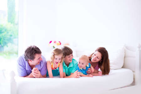 Young family with three kids at home in bed. Parents with children relaxing in bed on a sunny morning. Mother, father, baby boy, toddler girl and school child together. White interior and bedding.