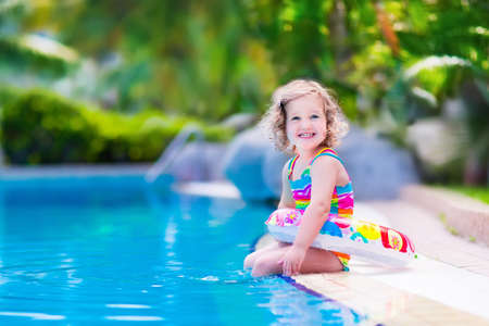 Kids in swimming pool. Children swim outdoors. Toddler child during vacation in a tropical resort with palm trees. Little girl playing on a beach. Active kid in summer with colorful toy floating ring. 스톡 콘텐츠
