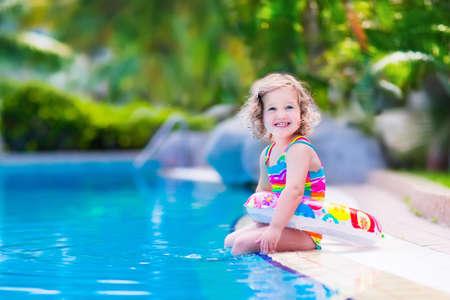 mignonne petite fille: Les enfants dans la piscine. Les enfants nagent en plein air. enfant en bas âge pendant les vacances dans un complexe tropical avec des palmiers. Petite fille jouant sur une plage. Kid Actif en été avec le jouet coloré anneau flottant. Banque d'images