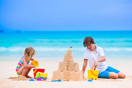 Kids playing on a beach. Two children build a sand castle at the sea shore. Family vacation on a tropical island. Boy and girl digging with toy spade and kid spade. Traveling with young child.