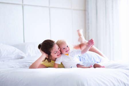 Moeder en baby in bed. Jonge moeder spelen met haar pasgeboren zoon. Kind en ouder samen thuis. Gezin met kinderen in de ochtend. Vrouw met kind in een zonnige slaapkamer. Geluk en moederschap
