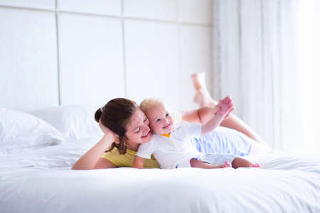 comfortable: Mother and baby in bed. Young mom playing with her newborn son. Child and parent together at home. Family with kids in the morning. Woman relaxing with kid in a sunny bedroom. Happiness and motherhood