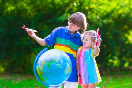 school age boy: Two happy children, cute curly toddler girl and a smiling school age boy play with toy airplanes flying over the globe dreaming of traveling around the world. Kids fly and travel with airplane. Stock Photo