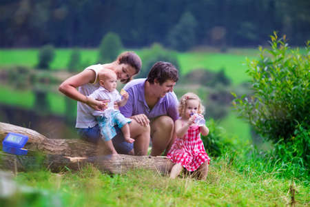 Family on summer hike. Young parents with kids hiking next to a lake. Mother, father and two children having picnic outdoors. Active trekking with baby and toddler. Beautiful nature of Germany.