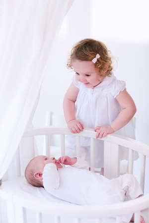 bassinet: Kids in bed. Two children playing together in a white sunny bedroom. Little girl meets her newborn baby brother. Siblings play indoors. Infant boy in a white bassinet with his sister. Kid in a crib.