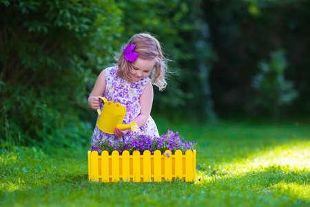 flor morada: Niño que trabaja en el jardín. Niños jardinería. Los niños regar las flores. Niña con la lata de agua sobre un césped verde en el jardín en verano. Niño del niño que juega al aire libre plantación púrpura macetas. Foto de archivo