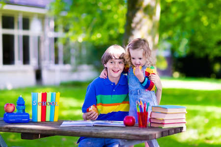 niño con mochila: Niño en la escuela. Muchacho adolescente estudiante inteligente y preescolar niña estudiando y aprendiendo al aire libre, la lectura de libros y tener la manzana para la merienda saludable. Niños felices de estar de vuelta a la escuela. Los niños en una clase. Foto de archivo