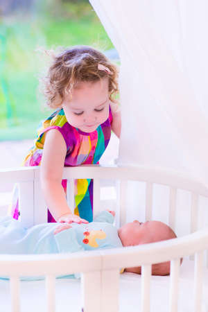 sleeping kid: Kids in bed. Two children playing together in a white sunny bedroom. Little girl meets her newborn baby brother. Siblings play indoors. Infant boy in a white bassinet with his sister. Kid in a crib.