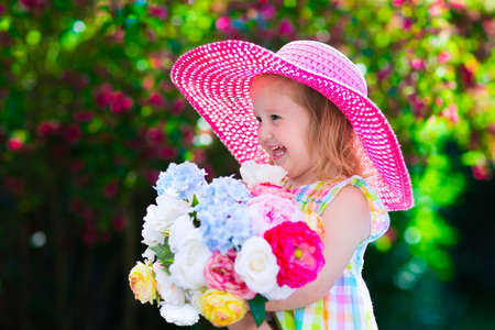 flores de cumpleaños: Pequeña muchacha linda con flores. Niño que lleva un sombrero de color rosa jugando en un jardín de verano en flor. Niños jardinería. Los niños juegan al aire libre. Chico Niño con el ramo de flores para el cumpleaños o el día de madre? S.