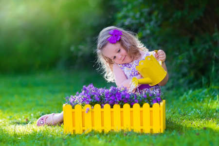 정원에서 일하고 아이. 아이들은 정원. 아이들은 꽃에 물을. 여름에 뒤뜰에서 녹색 잔디에 물을 수있는 어린 소녀. 유아 아이 야외 연주 보라색 꽃 화분