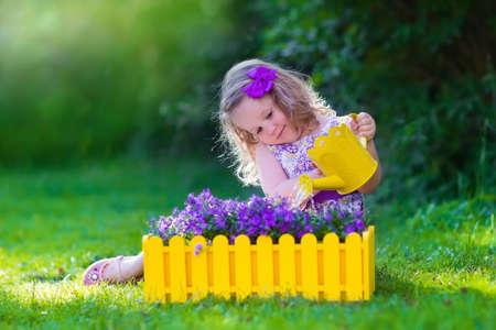 Pflanzen: Kind im Garten arbeitet. Kindergartenarbeit. Kinder Blumen gießen. Kleines Mädchen mit Wasser auf einem grünen Rasen im Garten im Sommer. Kleinkind Kind spielen im Freien Pflanzen von lila Blumentöpfe. Lizenzfreie Bilder
