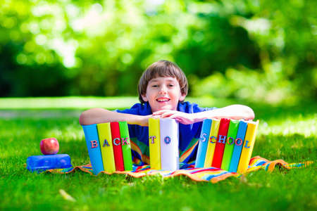 Child in school yard. Smart teenager student boy studying and learning outdoors, reading books and having apple for healthy snack. Kids happy to be back to school. Children in a class. Stock Photo