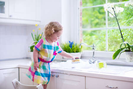 contemporary house: Child washing dishes. Kids wash plates and cups. Little girl helping in the kitchen playing with water and foam in a white sink with retro tap. Chores for children. Modern home interior with window.