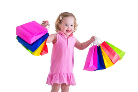 Holčička v růžových šatech drží barevné nákupní tašky. Dítě v obchodě nákup oblečení. Prodej v obchodě. Děti s nákupy.