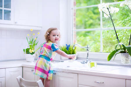 Child washing dishes. Kids wash plates and cups. Little girl helping in the kitchen playing with water and foam in a white sink with retro tap. Chores for children. Modern home interior with window.