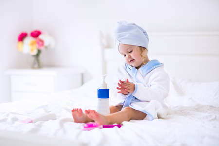 Child after bath. Cute little girl with wet curly hair wearing a bathrobe and head towel sitting on a white bed using lotion and brush. Hygiene for kids. Bathroom textile for babies and children. Stock Photo