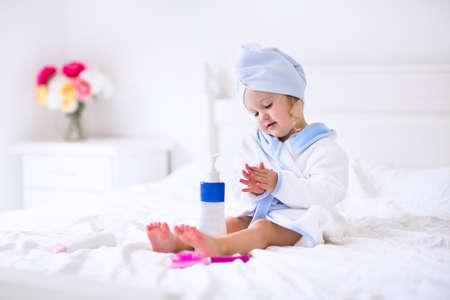 toalla: Niño después del baño. Niña linda con el pelo rizado húmedo con una toalla de baño y la cabeza sentado en una cama blanca usando la loción y el pincel. Higiene para los niños. Cuarto de baño textiles para bebés y niños.