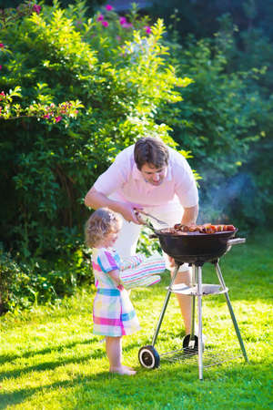 fiesta familiar: Padre e hijo asar carne. Camping familiar y disfrutar de la barbacoa. Papá e hija en la barbacoa preparar carnes y embutidos. Los padres y los niños comiendo comida parrilla al aire libre. Diversión jardín para los niños.