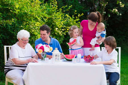 Big family with children have lunch outdoors. Parents with 3 kids and grandmother eat in the garden. Picnic for mother, father, baby boy, toddler girl and teenager child. Generations and retirement. Imagens