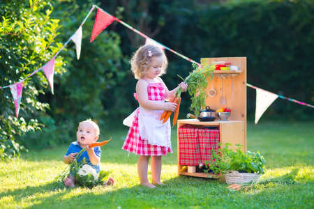 home and garden: Kids playing with a toy kitchen. Children play in a summer garden. Boy and girl cooking and baking healthy vegetables in the backyard. Toddler child and baby cook together. Outdoor fun in summer.